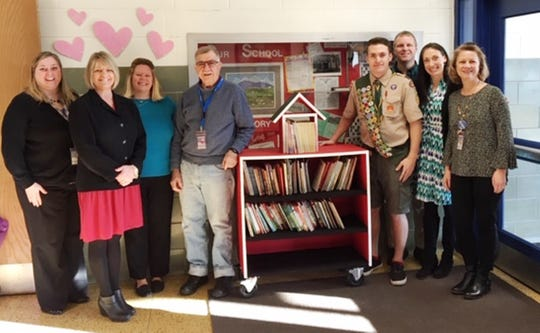 Chambersburg senior Donovan Hazelton shows the mobile library he created for Falling Spring Elementary School as part of his effort to become an Eagle Scout. He is pictured with school and district officials.