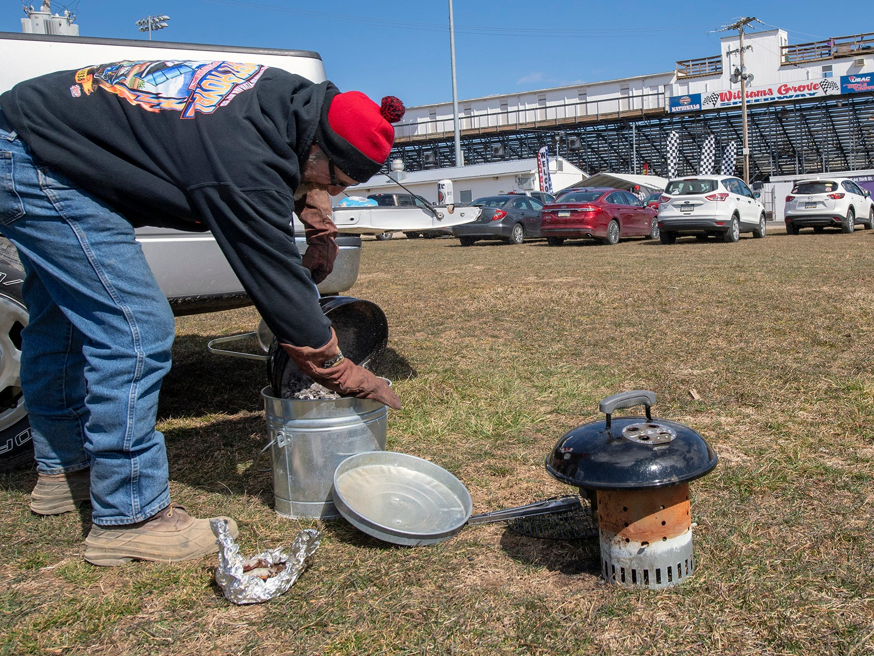 Bruce Reaser, of Schuylkill County, cooked burgers inthe parking lot for a tailgate party before the Williams Grove season opener for 410 sprints Sunday March 17, 2019.