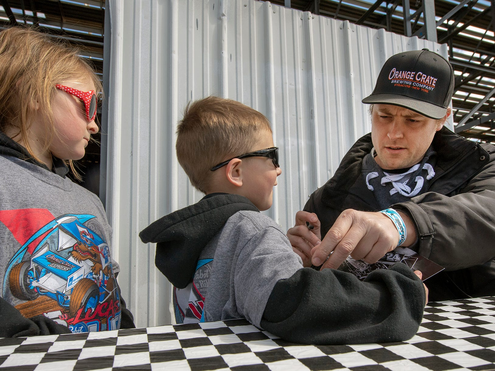 From the right, Lucas Wolfe signs shirts for Tripp, age 4, and Piper Hartz of Wapwallopen before the Williams Grove season opener for 410 sprints Sunday March 17, 2019. Wolfe went on to win the feature event.