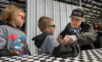 Fans talk about their favorite drivers as the opening 410 sprints run in the background at Williams Grove Speedway