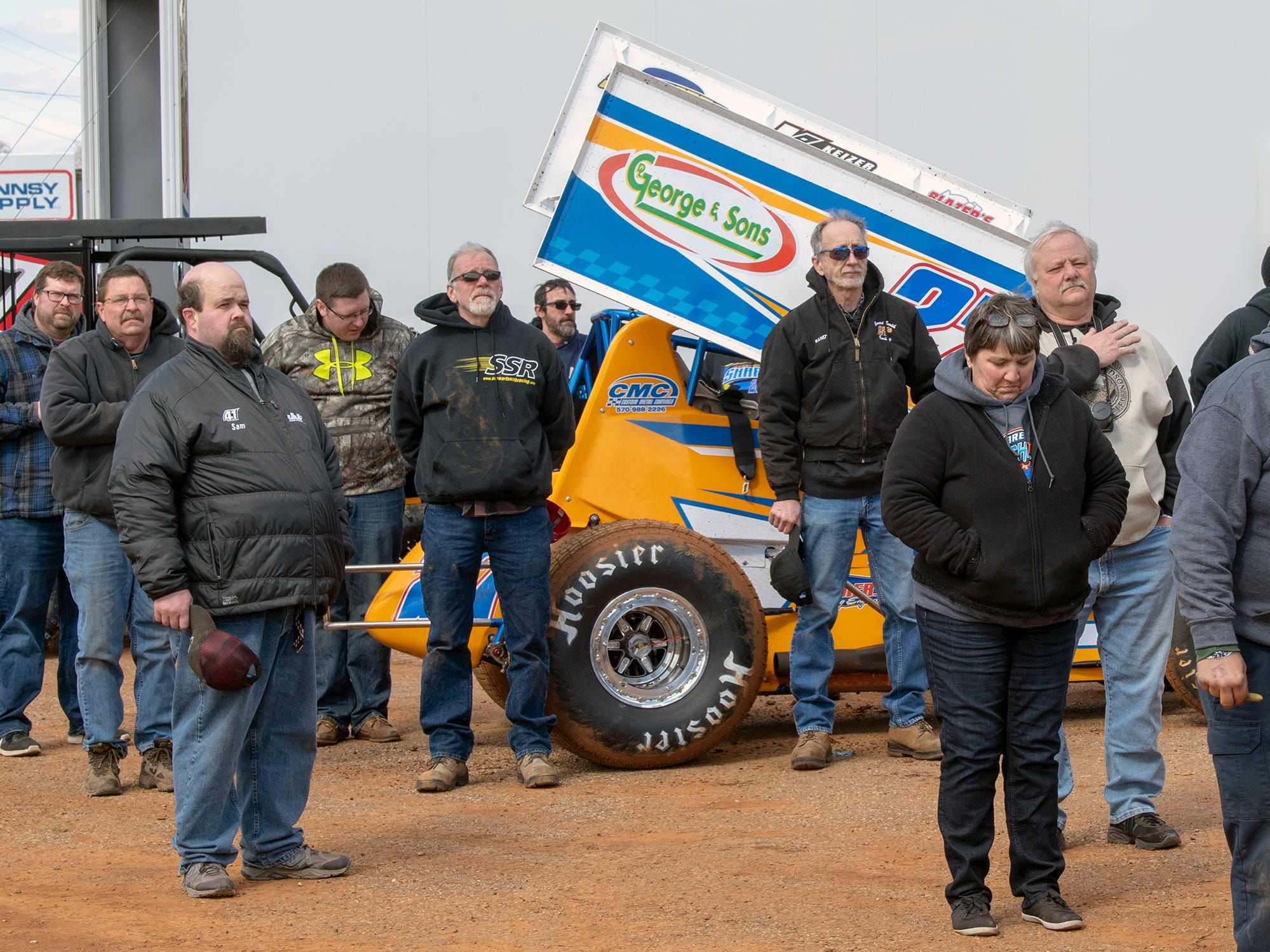 Pit teams pause a moment during the National Anthem before the Williams Grove season opener for 410 sprints Sunday March 17, 2019.