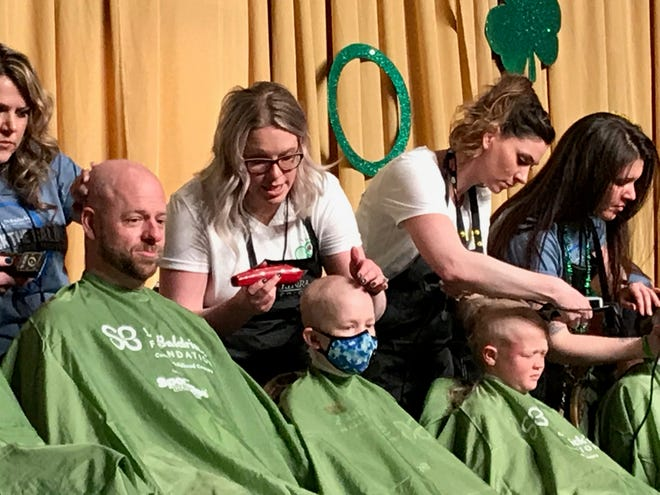Vaughn Spencer, 11, (middle) shaves his head as part of the 14th annual St. Baldrick's Foundation head-shaving event held at the downtown Reno Ballroom on March 15, 2019.
