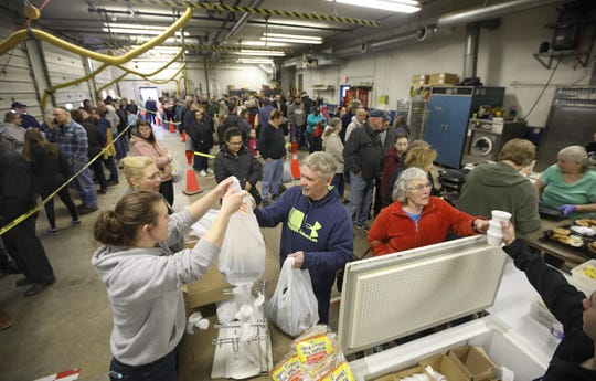 Hundreds of hungry customers make their way through a line snaking through the truck bays at the Fairville Fire Department on Friday, March 15, 2019. The winding line on the right is for take out orders, while the straight line at the left waits to dine on fish fry in the fire hall.