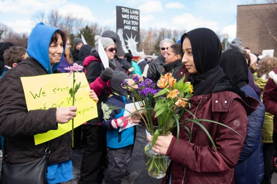 Alisha Khan, right, hands out flowers to people who gathered in front of the Islamic Center of Rochester on Sunday, March 17, 2019, in a show of support after a terrorist attack in New Zealand on Friday.