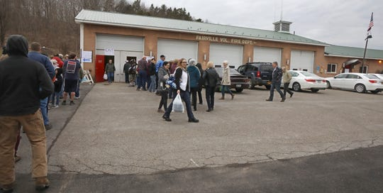 Hundreds wait in a line that stretches out the truck bays, down the parking lot and close to the road as they wait for the popular fish fry at the Fairville Fire Department on Friday, March 15, 2019.