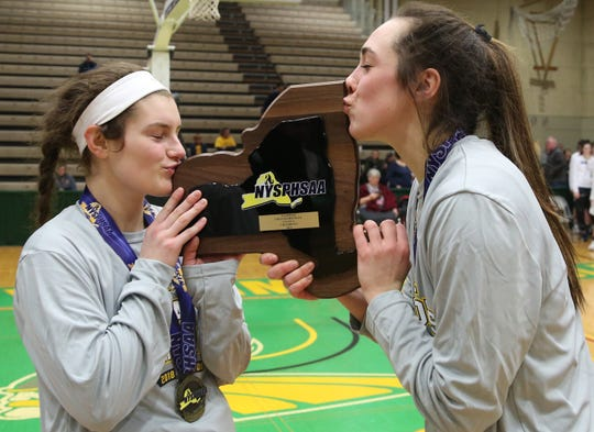 Pittsford Mendon players Ellie Mooney and Alana Fursman kiss the state championship plaque after defeating Seton Catholic 59-50 in the girls Class A state championship game at Hudson Valley Community College in Troy March 17, 2019.