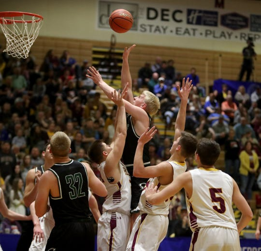 Clark-Willow Lake's Jacob Prouty, center, goes up with a shot between De Smet's Ethan McCune, left and Kalen Garry, right, during Saturday night's championship game at the South Dakota Class B boys basketball tournament at Wachs Arena.