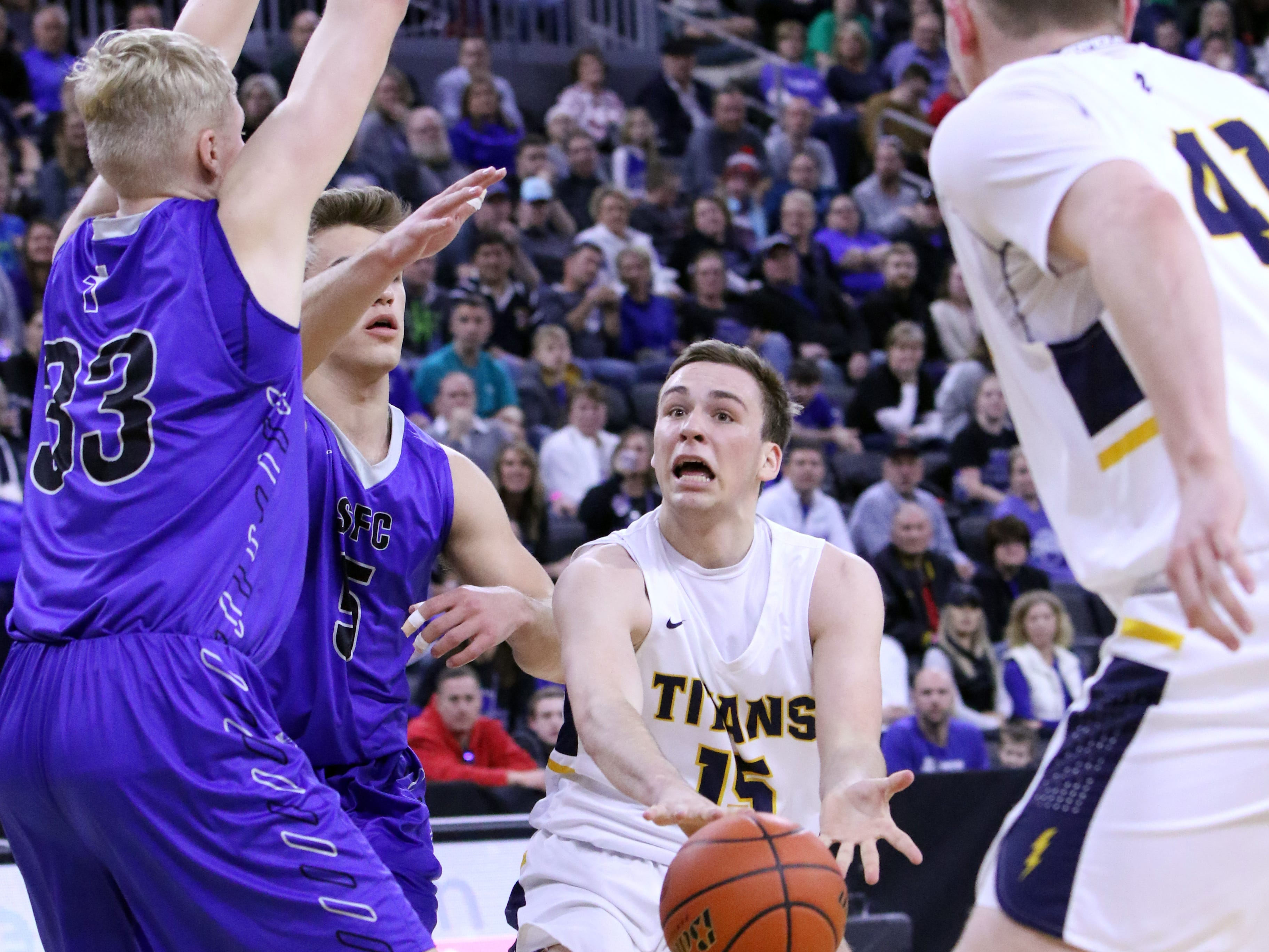 Noah Freidel of Tea Area dishes the ball past Zach Witte of Sioux Falls Christian during Saturday's Class A title game at the Premier Center.