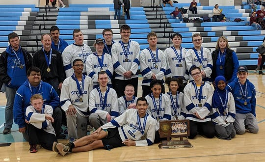 The St. Cloud Area Slapshots pose with their state championship trophy Saturday, March 16, 2019, at Bloomington Jefferson High School