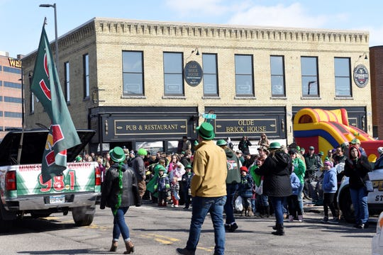 People gather outside Olde Brick House during the St. Patrick's Day parade on March 17, 2019.