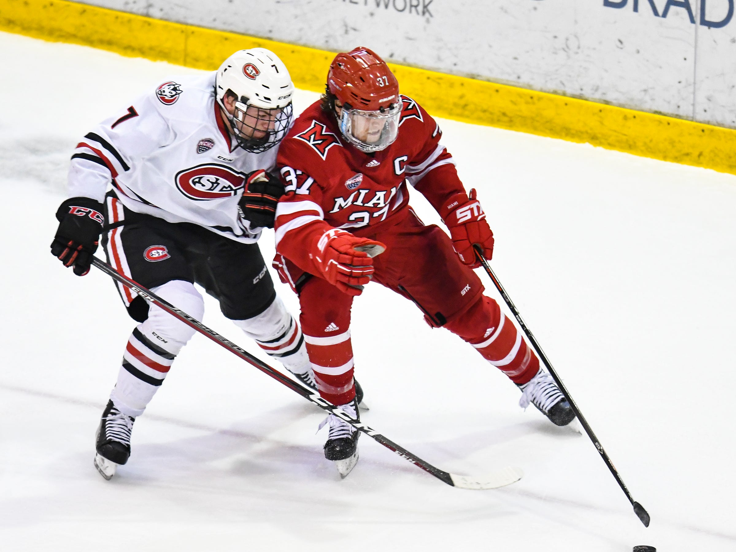 St. Cloud State's Nick Poehling and Josh Melnick of Miami struggle for control of the puck during the second period of the Saturday, March 16 game at the Herb Brooks National Hockey Center in St. Cloud.