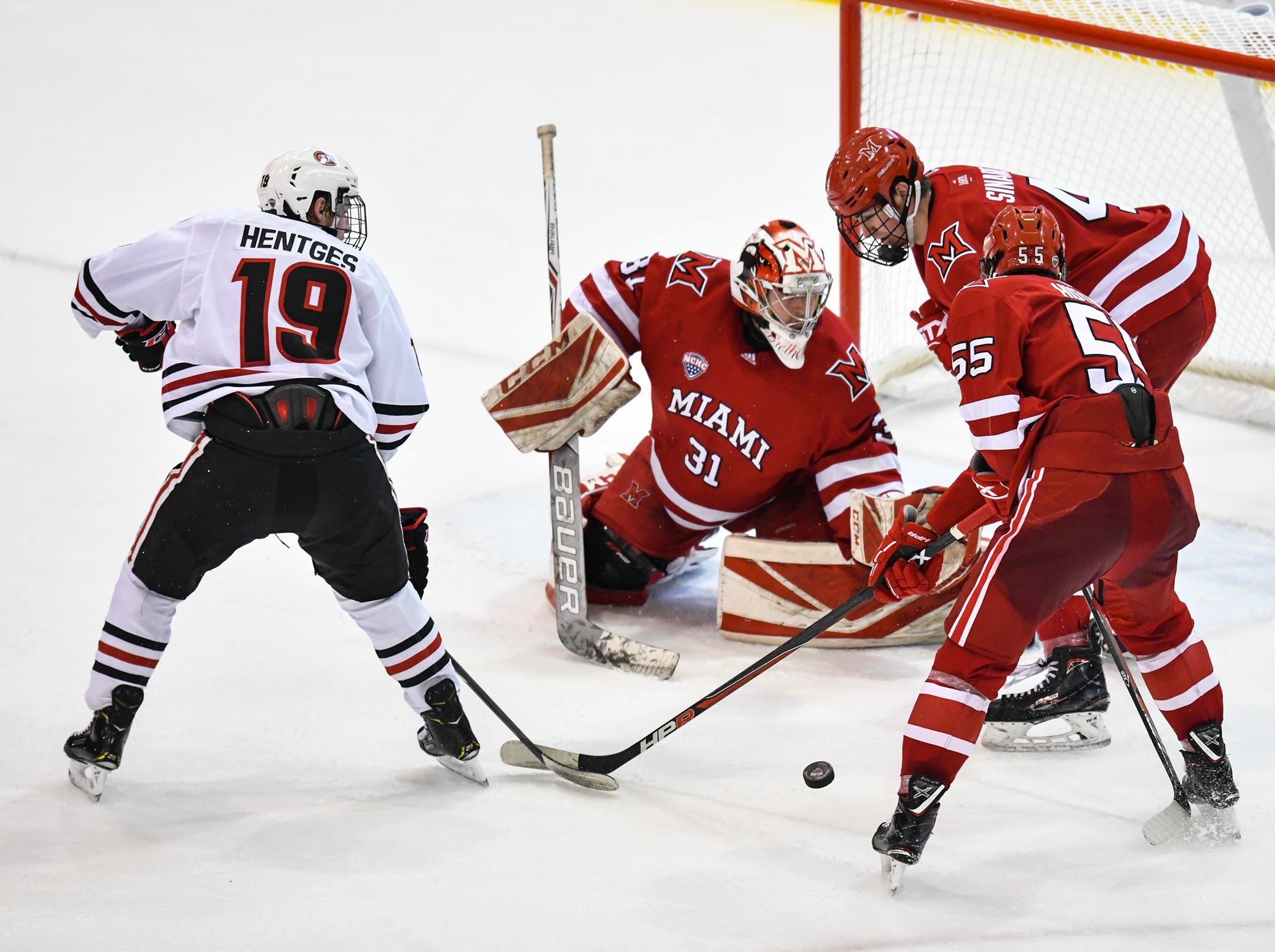 The puck bounces in front of St. Cloud State's Sam Hentges and Miami goaltender Ryan Larkin during the second period of the Saturday, March 16 game at the Herb Brooks National Hockey Center in St. Cloud.