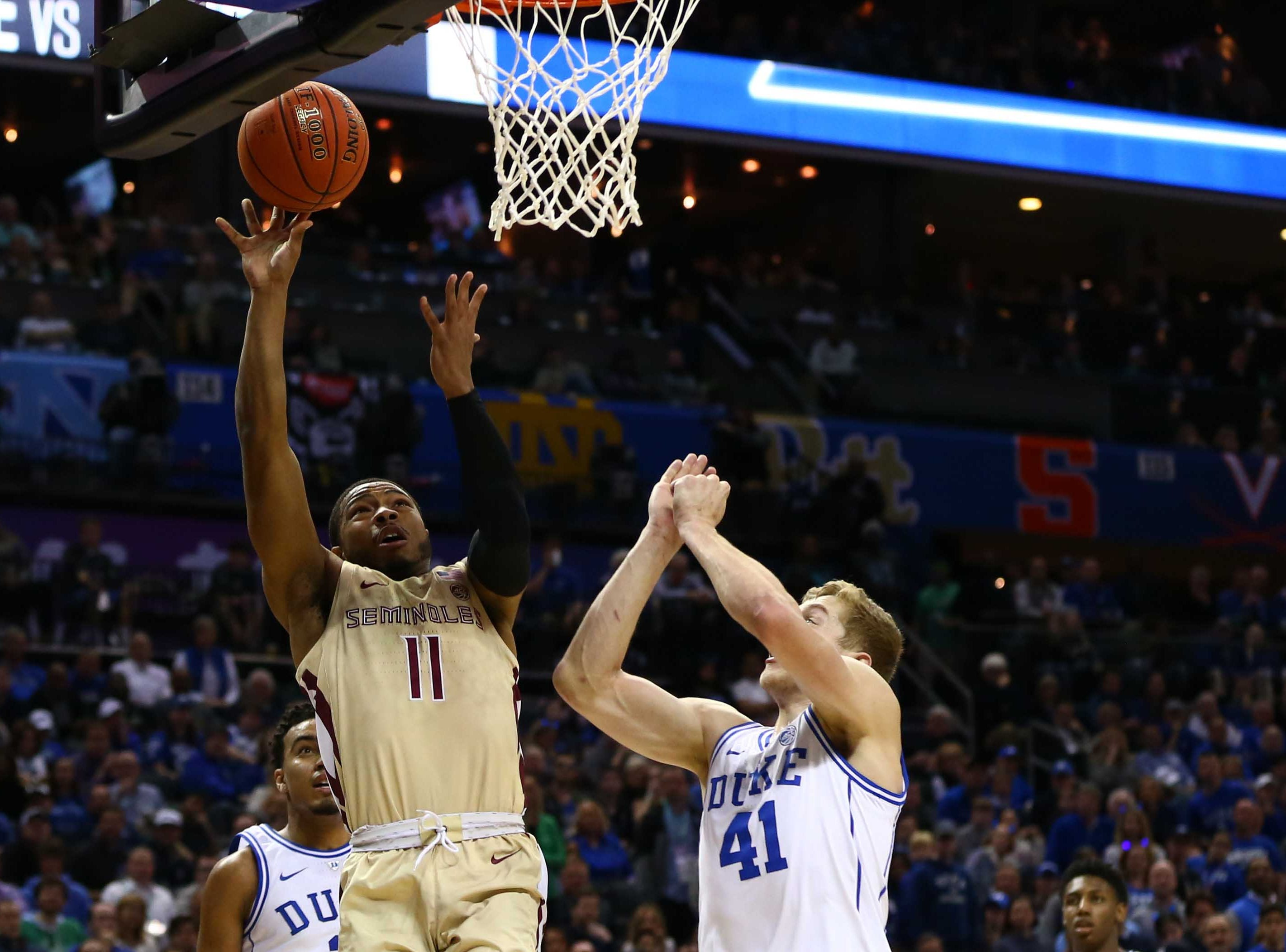 Mar 16, 2019; Charlotte, NC, USA; Florida State Seminoles guard David Nichols (11) shoots the ball against Duke Blue Devils forward Jack White (41) in the first half in the ACC conference tournament at Spectrum Center. Mandatory Credit: Jeremy Brevard-USA TODAY Sports