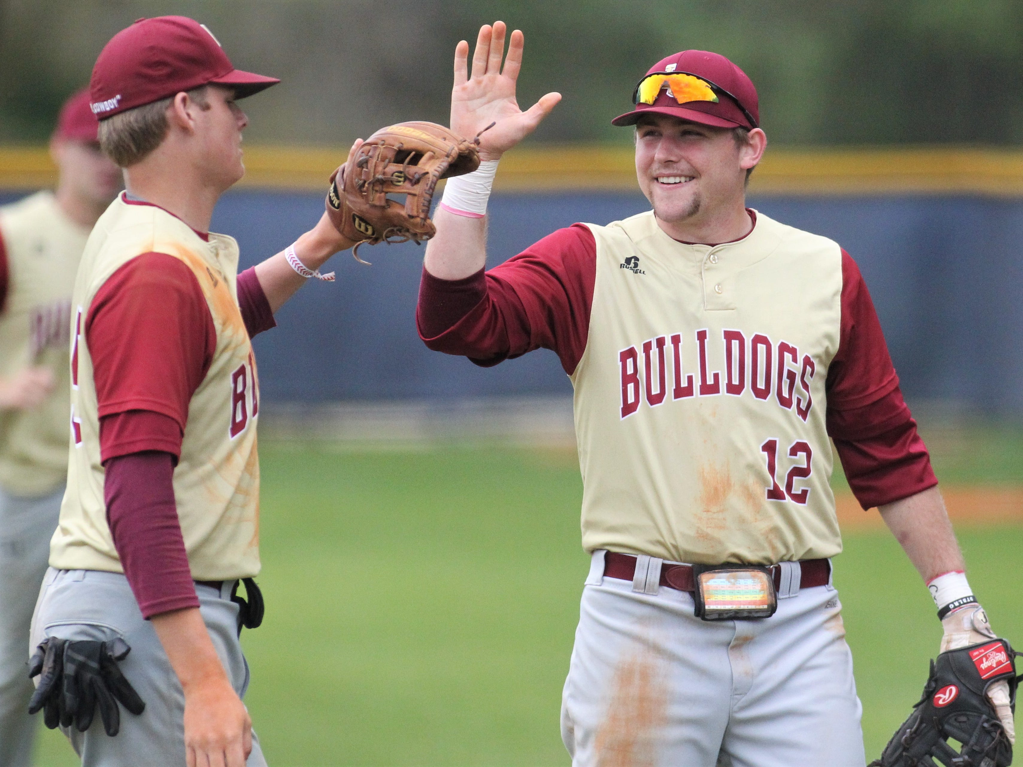 Liberty County first baseman Brady Peddie high fives Brice Dillmore as Liberty County's baseball team went on the road to beat Maclay 8-2 on Saturday, March 16, 2019. The Bulldogs played their first game following their head coach Corey Crum's tragic death six days ago.