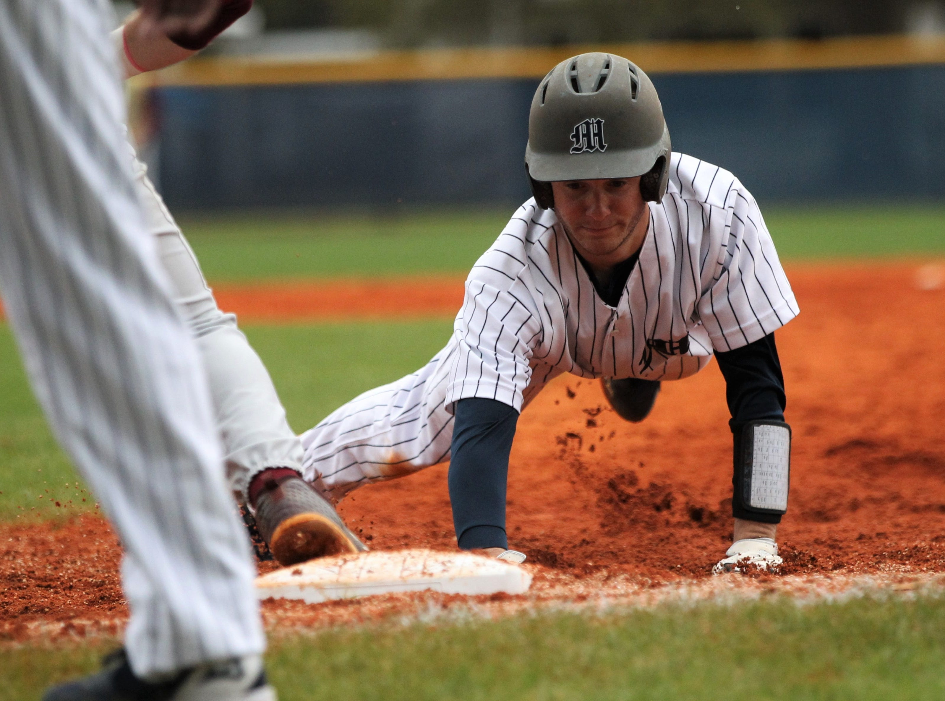 Maclay's Grant Harrison dives back into first base on a pick-off attempt as Liberty County's baseball team went on the road to beat Maclay 8-2 on Saturday, March 16, 2019. The Bulldogs played their first game following their head coach Corey Crum's tragic death six days ago.
