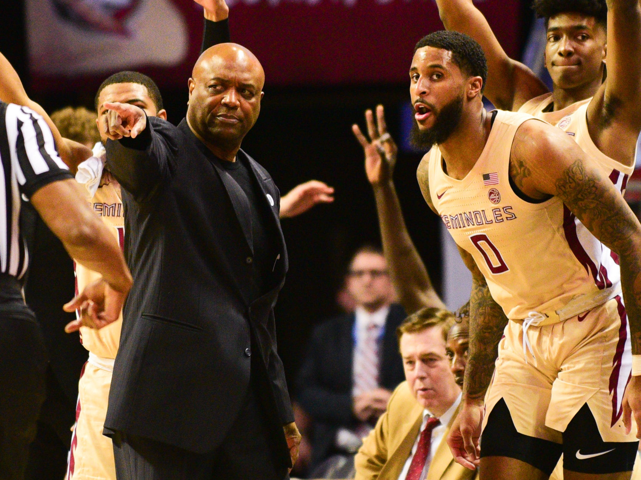 Florida State head coach Leonard Hamilton, left, directs redshirt senior forward Phil Cofer (0) back to the court during the first half of the ACC Championship game at the Spectrum Center on Saturday.