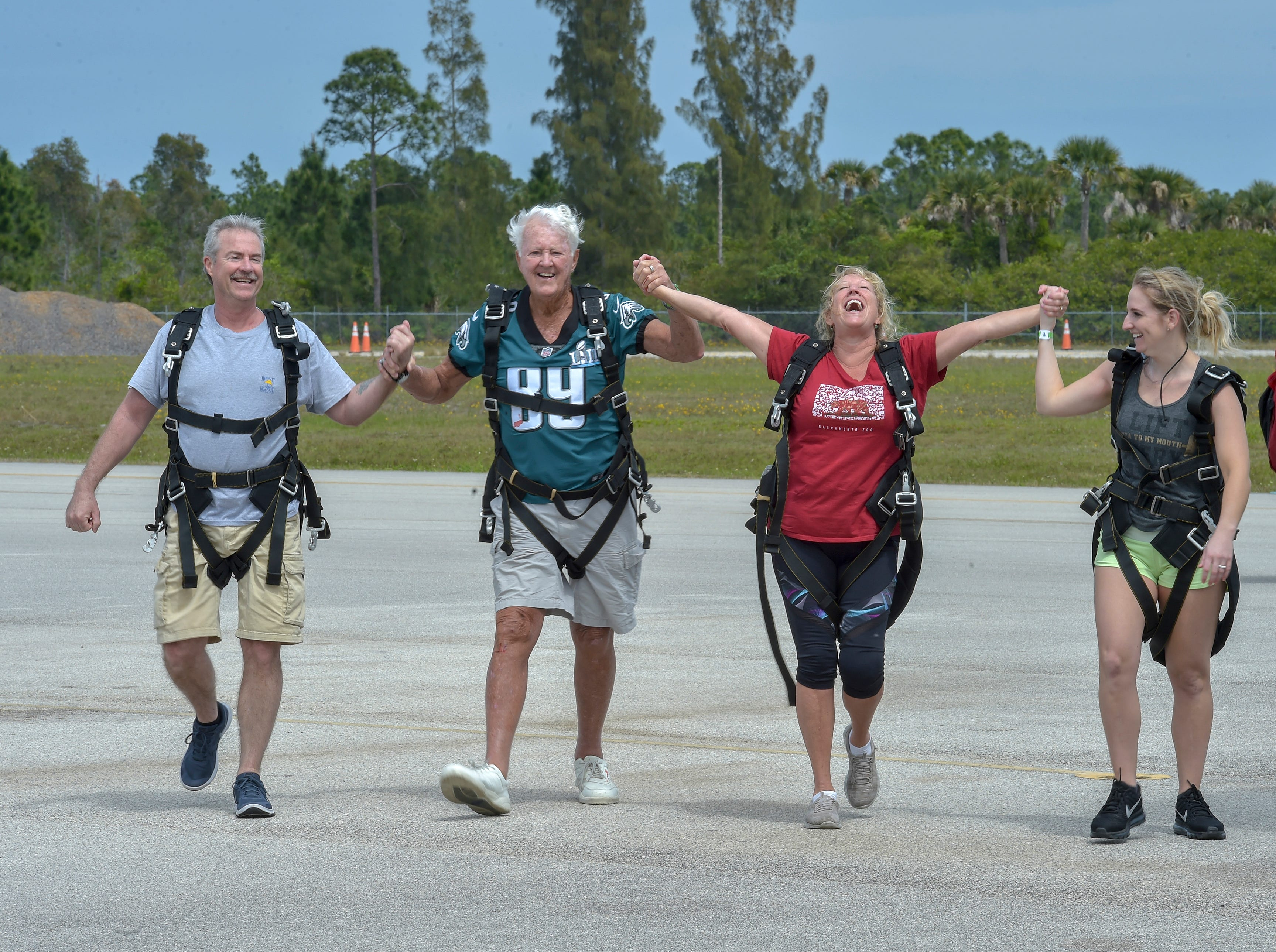 """Jack Grimner (second from left) a Port St. Lucie and St. Petersburg snowbird from Philadelphia, celebrate a successful skydive with (from left) his nephew Tom Grimmer, from Philadelphia, daughter Regina Grimner Robsahm, of Los Angelos, and great niece Kellie Grimner Mastria, of Montgomery County Pennsylvania, on Sunday, March 17, 2019, at Skydive Sebastian. Jack Grimner, a Philadelphia Eagles fan, made the jump to celebrate his 90th birthday on Saint Patrick's day, along with family members. """"President [H.W.] Bush did it, and I figured if he has enough nerve to do, it I certainly have,"""" Grimner said. """"So today is my 90th birthday and it's my bucket list idea to go."""" Grimner served in the U.S. Air Force as a lieutenant in the Air Defense Command."""