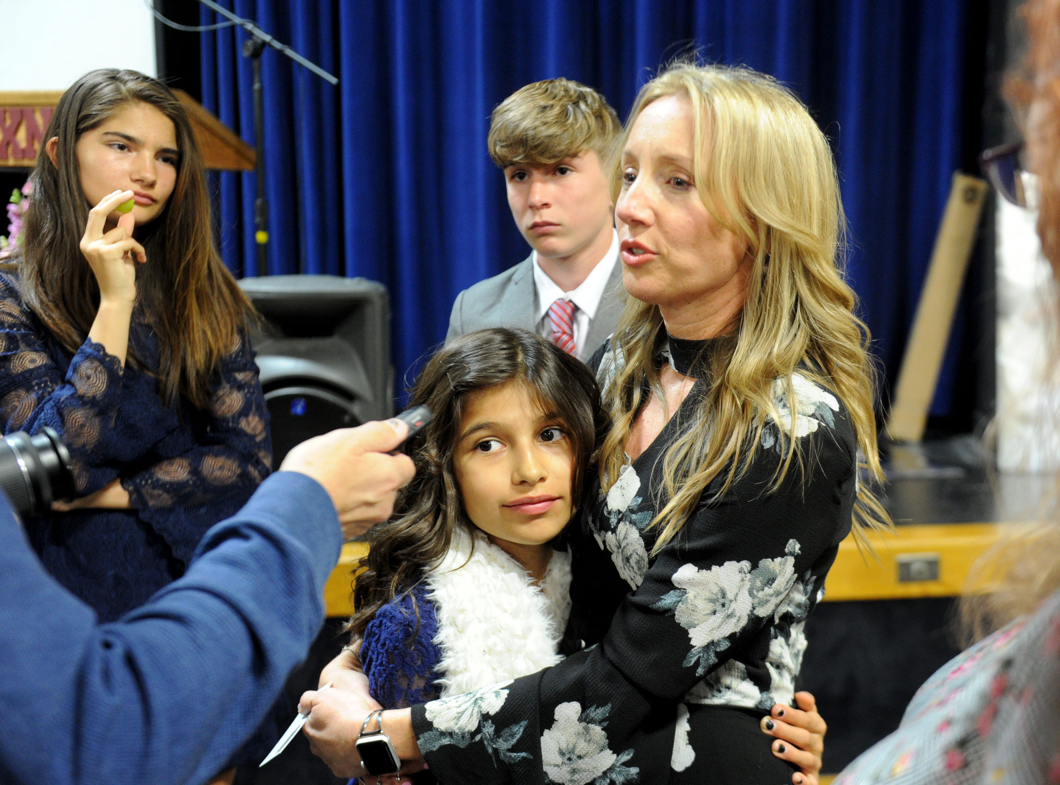 (Left to right) Lilah Rogers, Sofie Rogers and Braden Rogers watch their mom, Karen Rogers, speak with the media at the memorial service for Kimberly Lopez on Saturday in Oxnard.