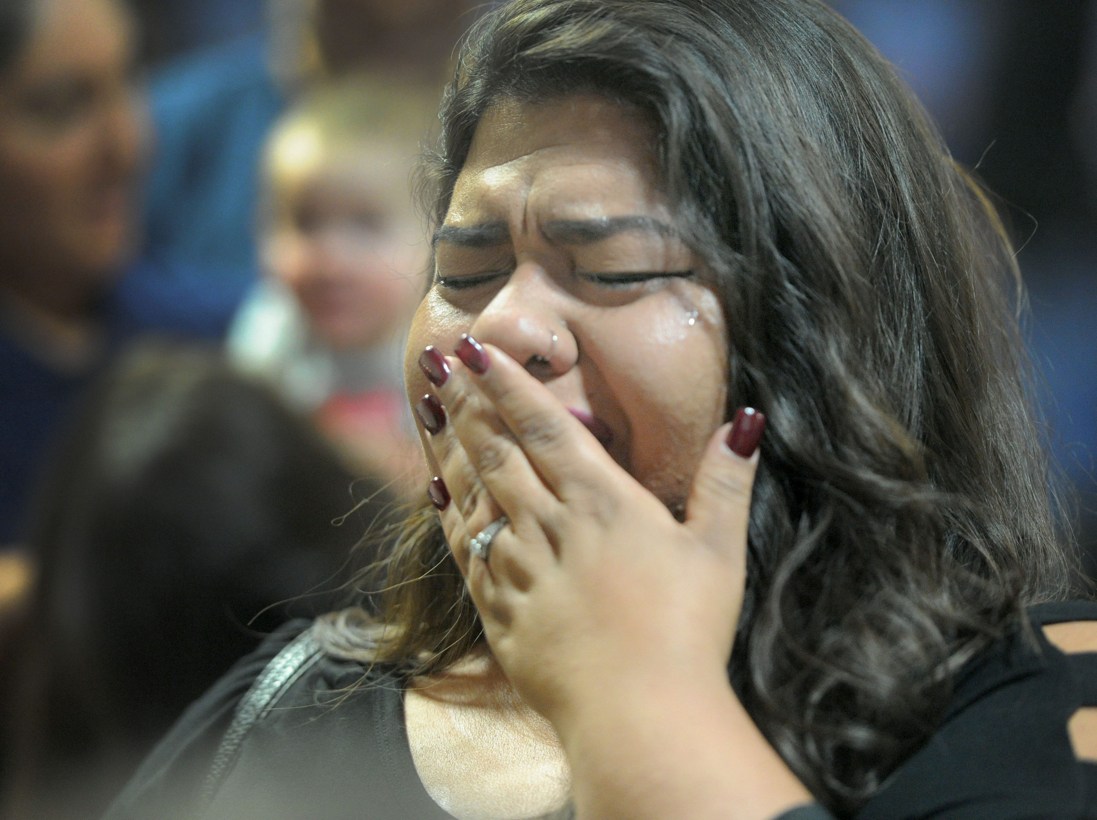 Maritza Serrato, who knew the Lopez family, cries at the memorial service for Kimberly Lopez on Saturday at the Oxnard High School Performing Arts Center.