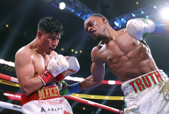 Mikey Garcia, left, takes a blow to the body from Errol Spence Jr. during the ninth round of their IBF welterweight championship bout Saturday in Arlington, Texas.