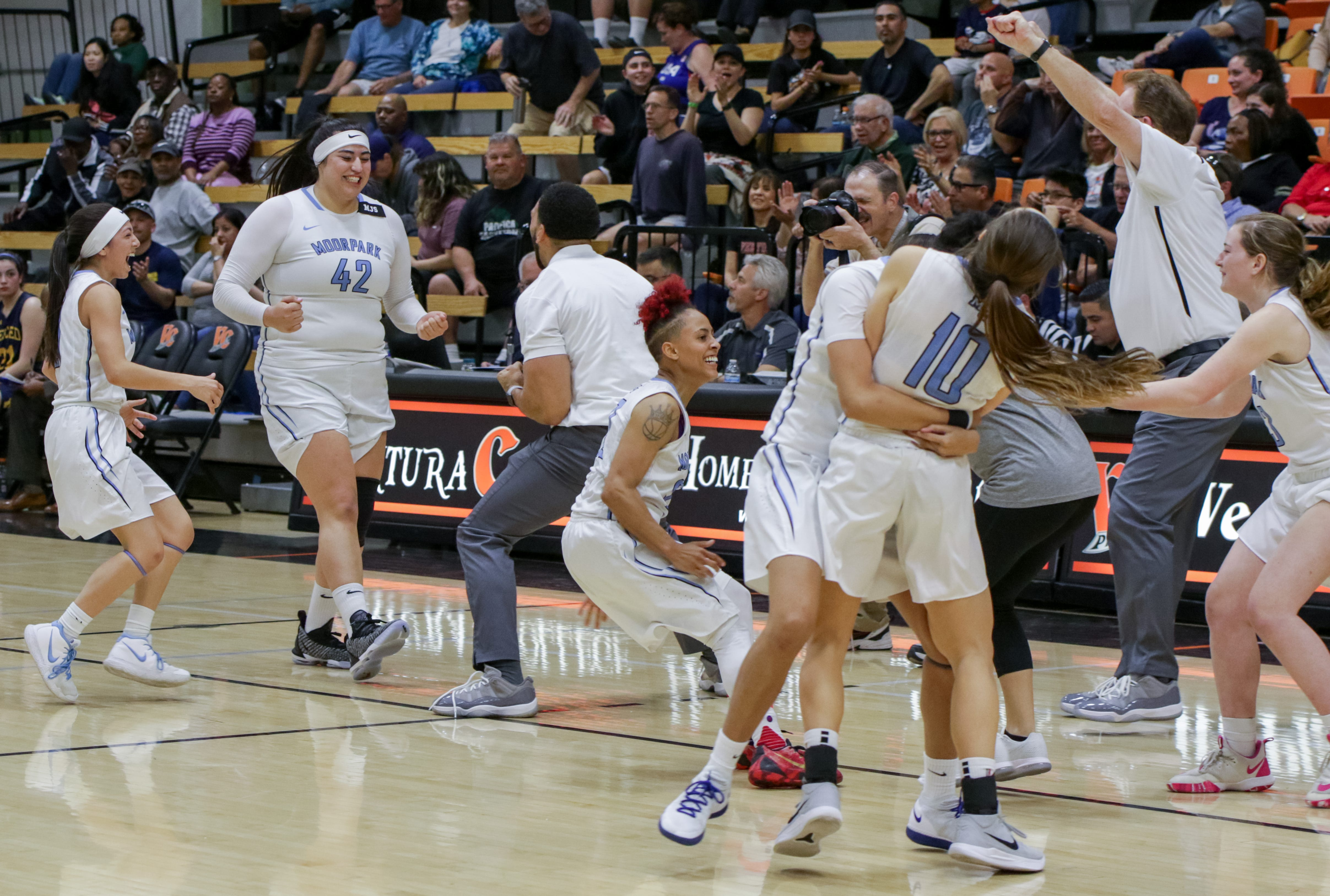 The Moorpark College women's basketball team celebrates advancing to the first CCCAA state final in program history after a 73-68 win over Merced College on Saturday night at Ventura College.