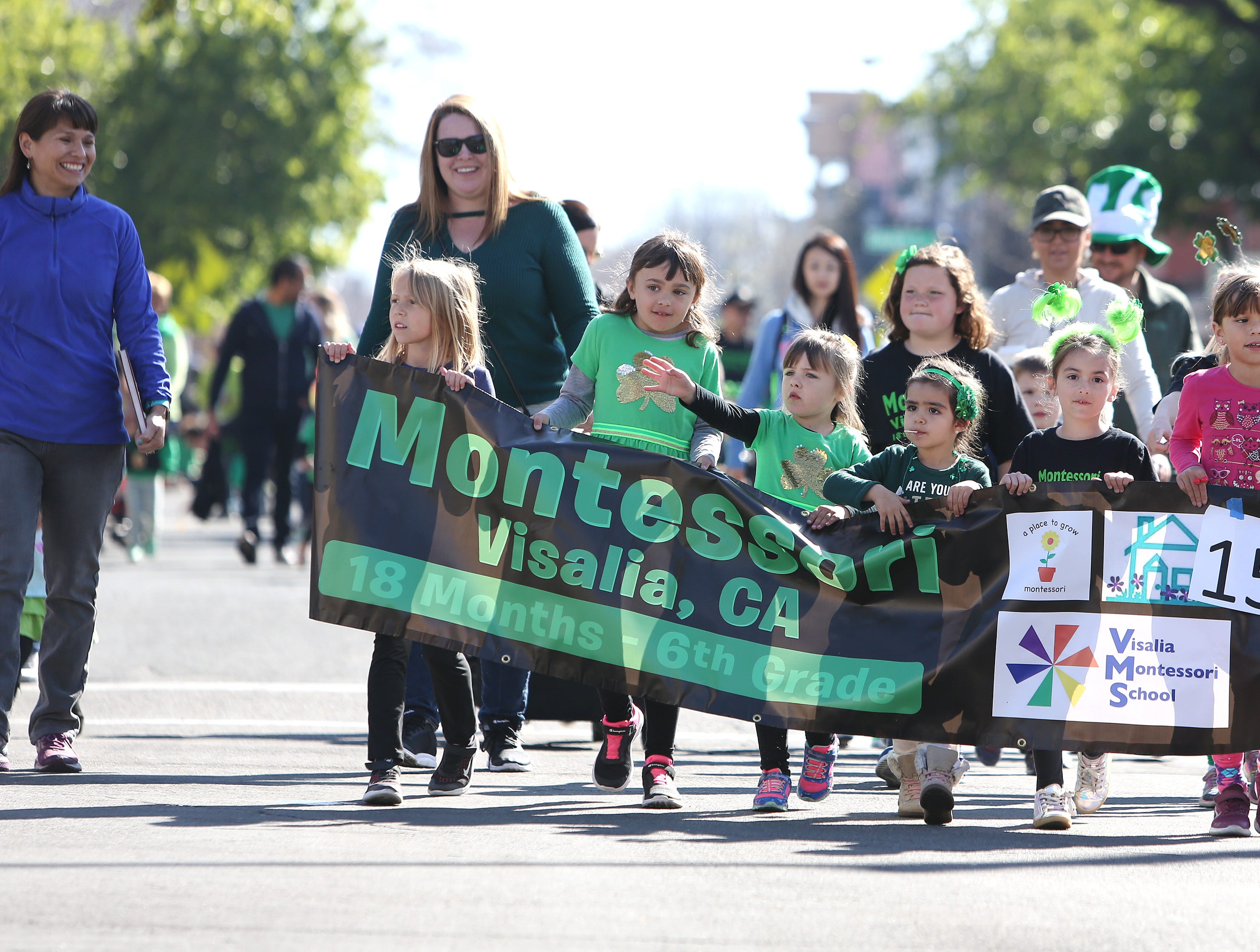 Montessori School attendee's wave to the crowds at this year's St. Patrick's Day parade rolling through Main Street Saturday, March 16, 2019 in Visalia, Calif.
