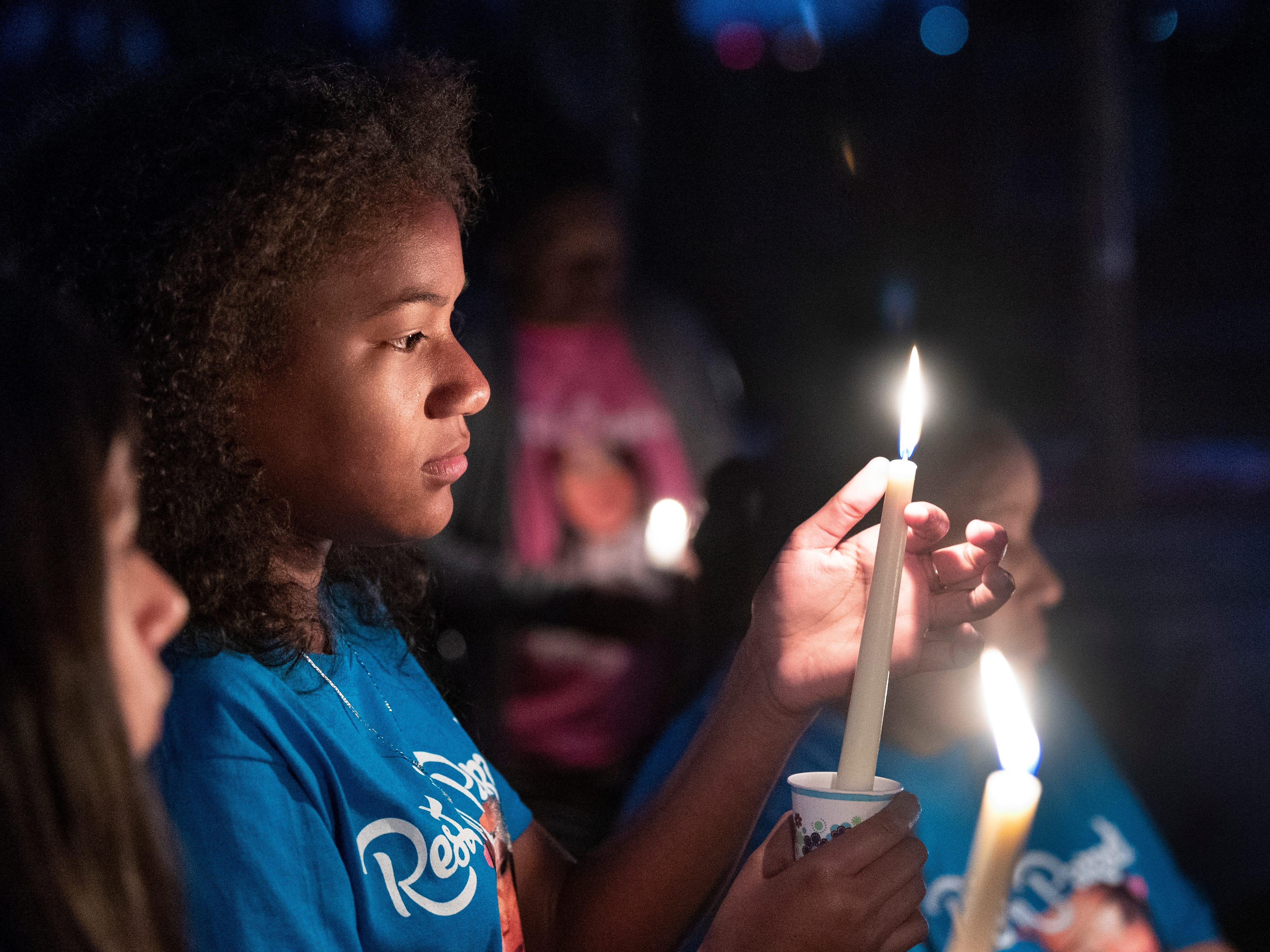 De'Ajah Hicks, 11, pauses with family and friends of her cousin Dynasty Alexander gathered at Elk Bayou Regional Park on Saturday, March 16, 2019. Birthday cake, a balloon release and a candle light vigil were offered in her memory. Alexander's body was found in an orchard outside of the city on March 3. She had been strangled and shot.