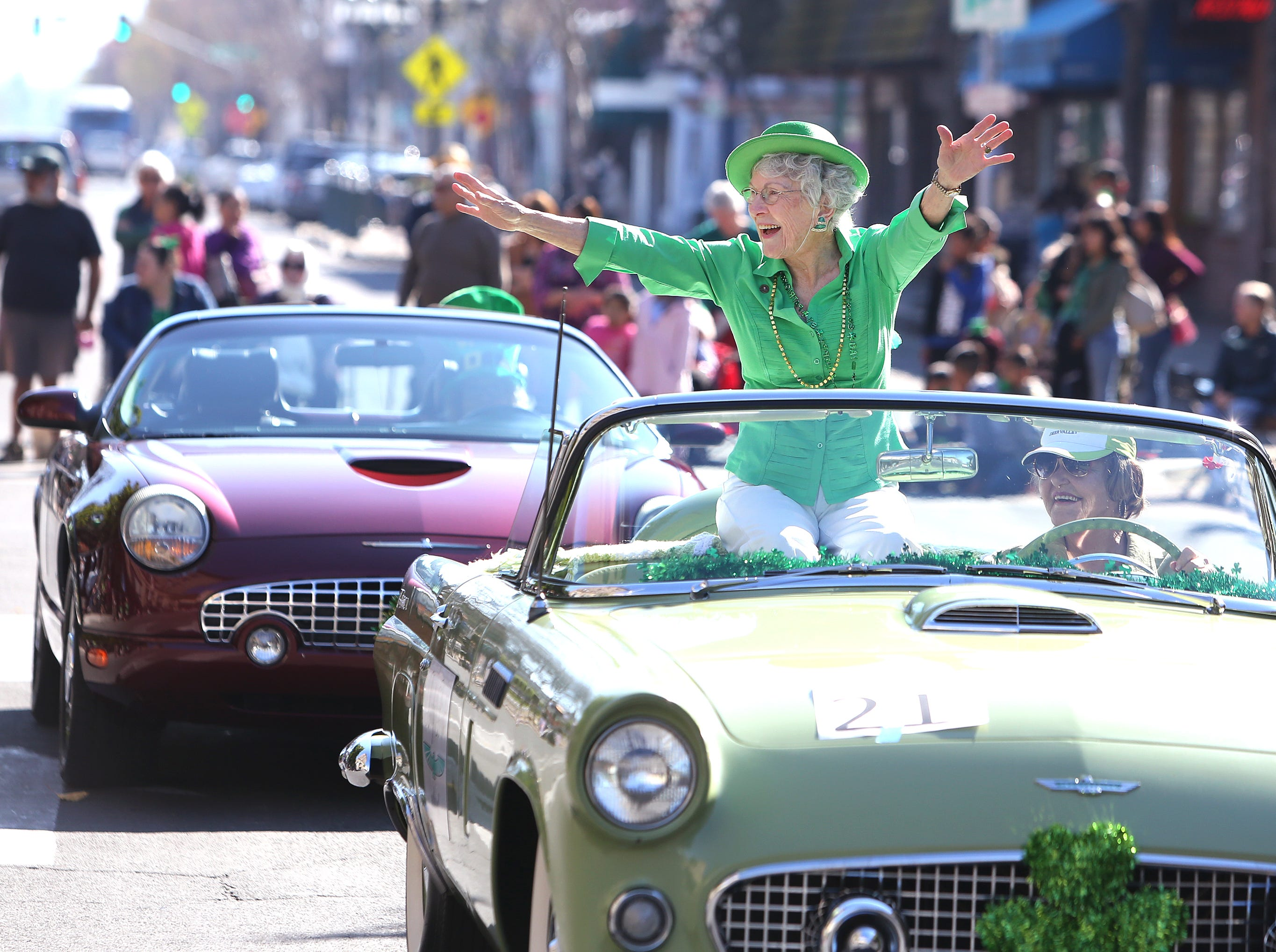JoAnn Miller from Valley Children's Hospital waves to the large crowds watching this year's St. Patrick's Day parade rolling through Main Street Saturday, March 16, 2019 in Visalia, Calif.