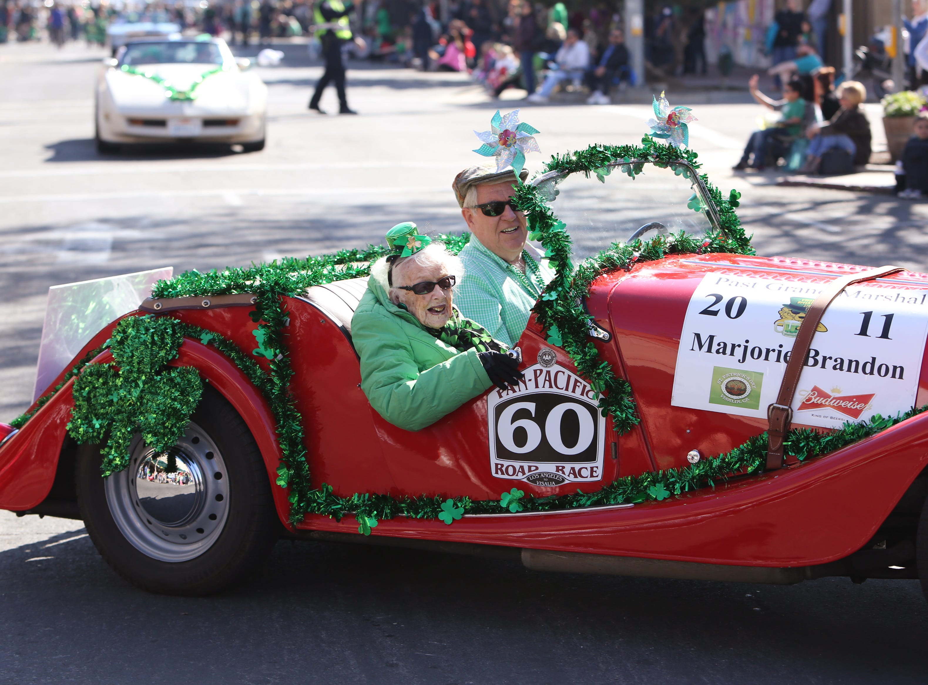 106 year old Marjorie Brandon waves to the overflowing crowds at this year's St. Patrick's Day parade rolling through Main Street Saturday, March 16, 2019 in Visalia, Calif.