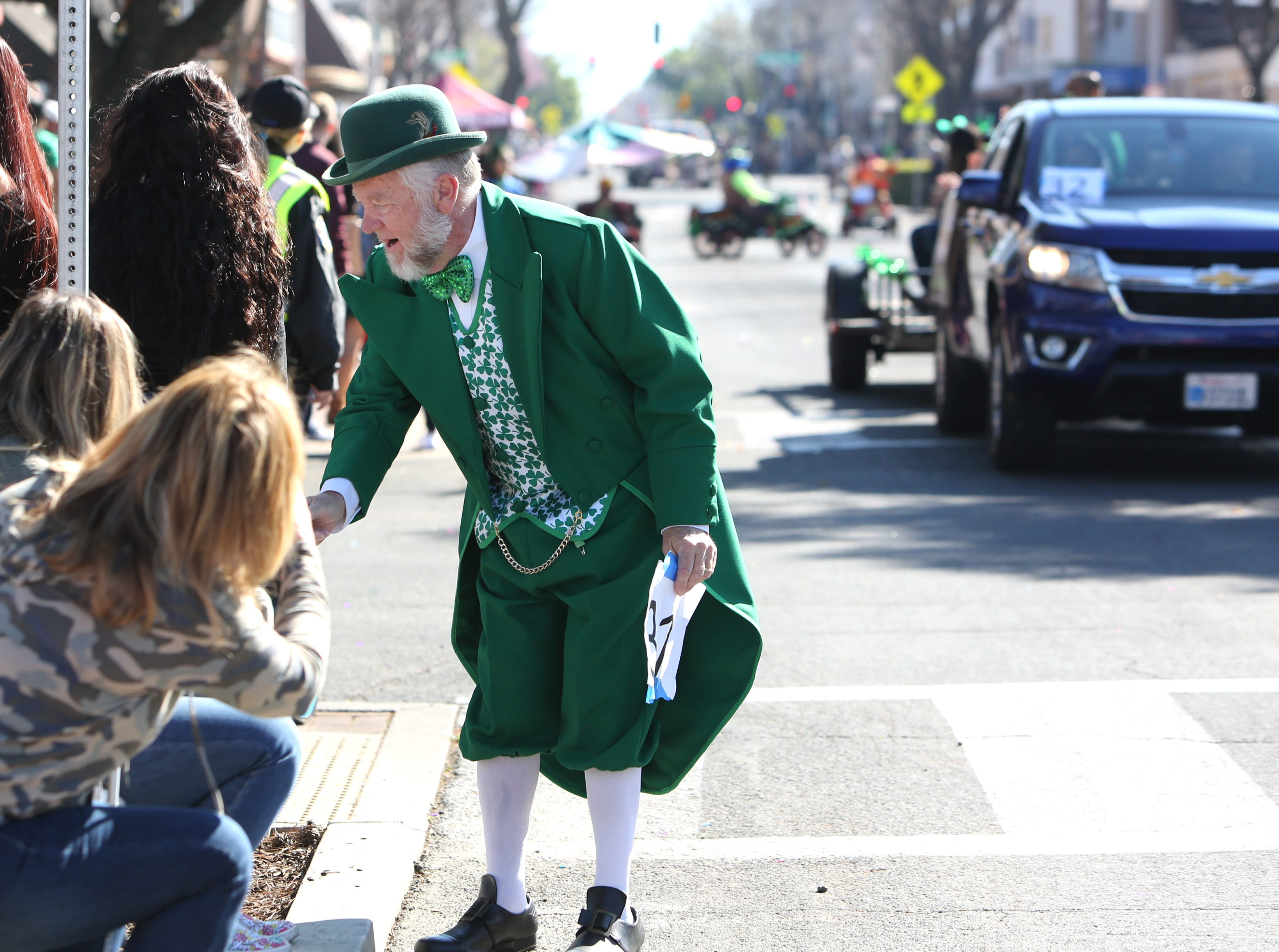 Bill Bates stops to shake hands with the crowds at this year's St. Patrick's Day parade rolling through Main Street Saturday, March 16, 2019 in Visalia, Calif.
