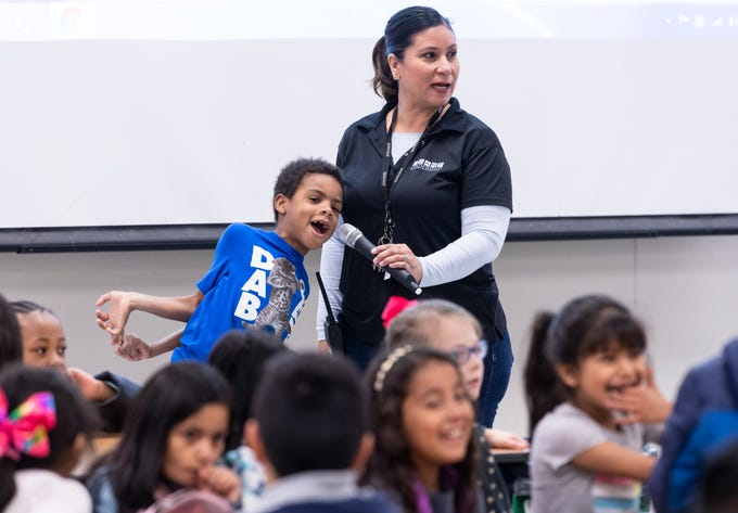 Jayvin Akins, 7, helps Noelia Avila start the Pro-Youth / HEART program for students at Viva Blunt School in Visalia on Wednesday, March 13, 2019.