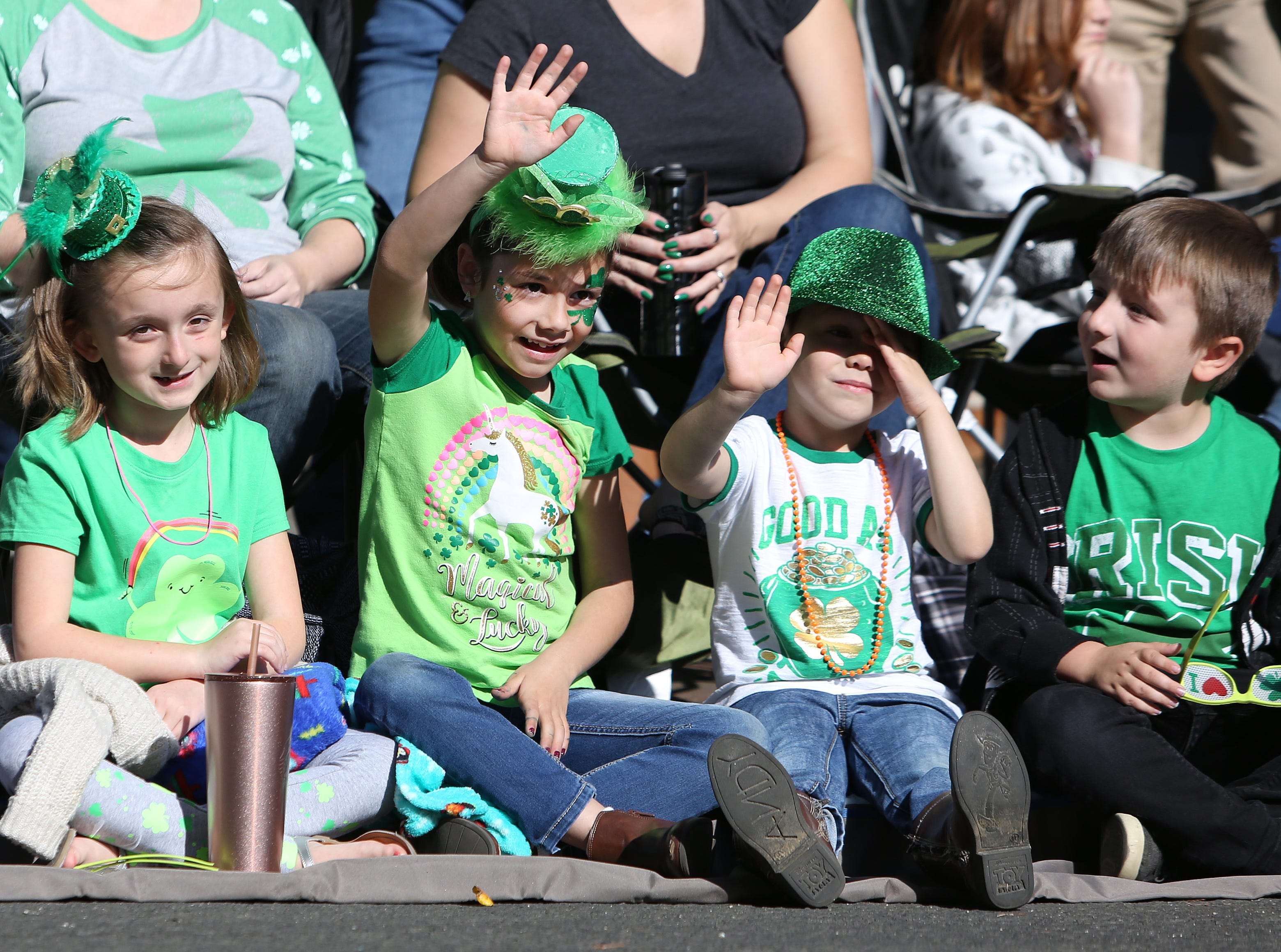 From left to right, Amber Lynn Mitchell, Aubrey and Grant Guerra, and Mason Mitchell enjoy the floats that pass by at this year's St. Patrick's Day parade rolling through Main Street Saturday, March 16, 2019 in Visalia, Calif.