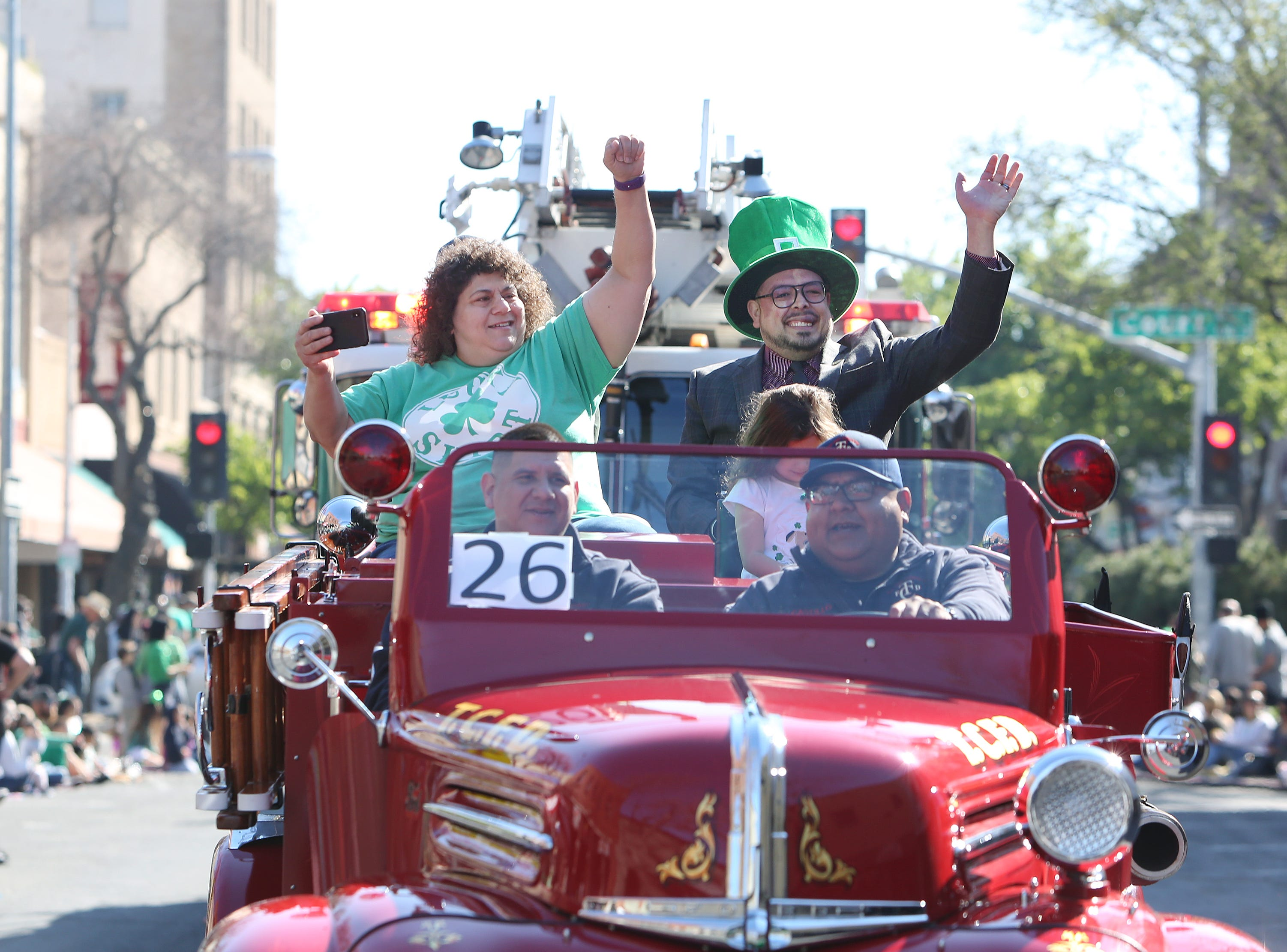Supervisors Amy Shuklian and Eddie Valero wave to the crowds at this year's St. Patrick's Day parade rolling through Main Street Saturday, March 16, 2019 in Visalia, Calif.