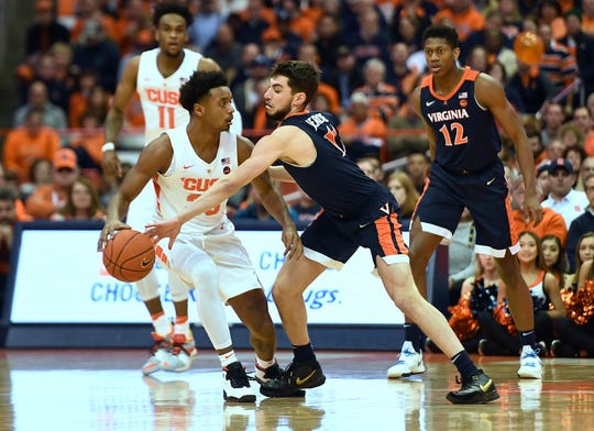 Syracuse forward Elijah Hughes, left, has the ball tipped away by Virginia guard Ty Jerome during the first half of an NCAA college basketball game in Syracuse, N.Y., Monday, March 4, 2019.