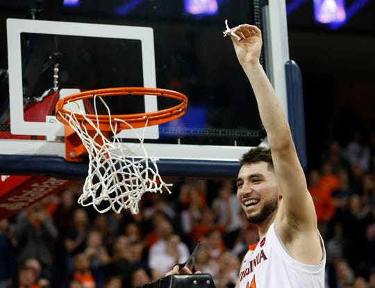 Virginia guard Ty Jerome (5) holds a piece of the net after his team defeated Louisville in Charlottesville, Va., Saturday, March 9, 2019. Virginia defeated Louisville 73-68.