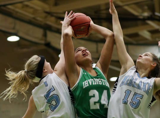 Irvington's Grace Thybulle (24) goes up for a shot between Midlakes 's Lydia Day (5) and Cara Walker (15) during the girls Class B state championship at Hudson Valley Community College in Troy March 16, 2019. Irvington won the game.