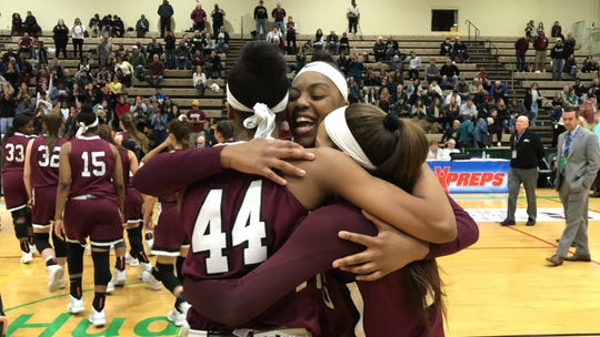 Ossining seniors Kailah Harris (center), Aubrey Griffin (left) and Jaida Strippoli (right) share a hug together after winning the Class AA state championship. Mar. 17, 2019.