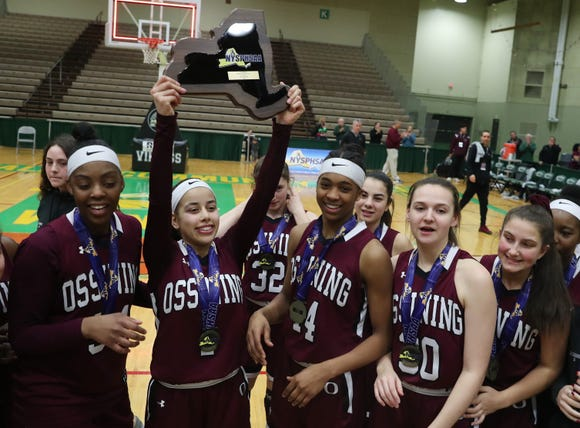 Ossining's Jaida Strippoli holds up the championship plaque as she celebrates with teammates after defeating West Genesee 93-46 in the girls Class AA state championship game at Hudson Valley Community College in Troy March 17, 2019.