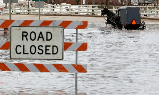 A man works his way through a flooded Galena Street as the Pecatonica River continues to rise in Darlington, Wis., Thursday, March 14, 2019.  The National Weather Service has issued a flood warning or flood watch for about two-thirds of the state.