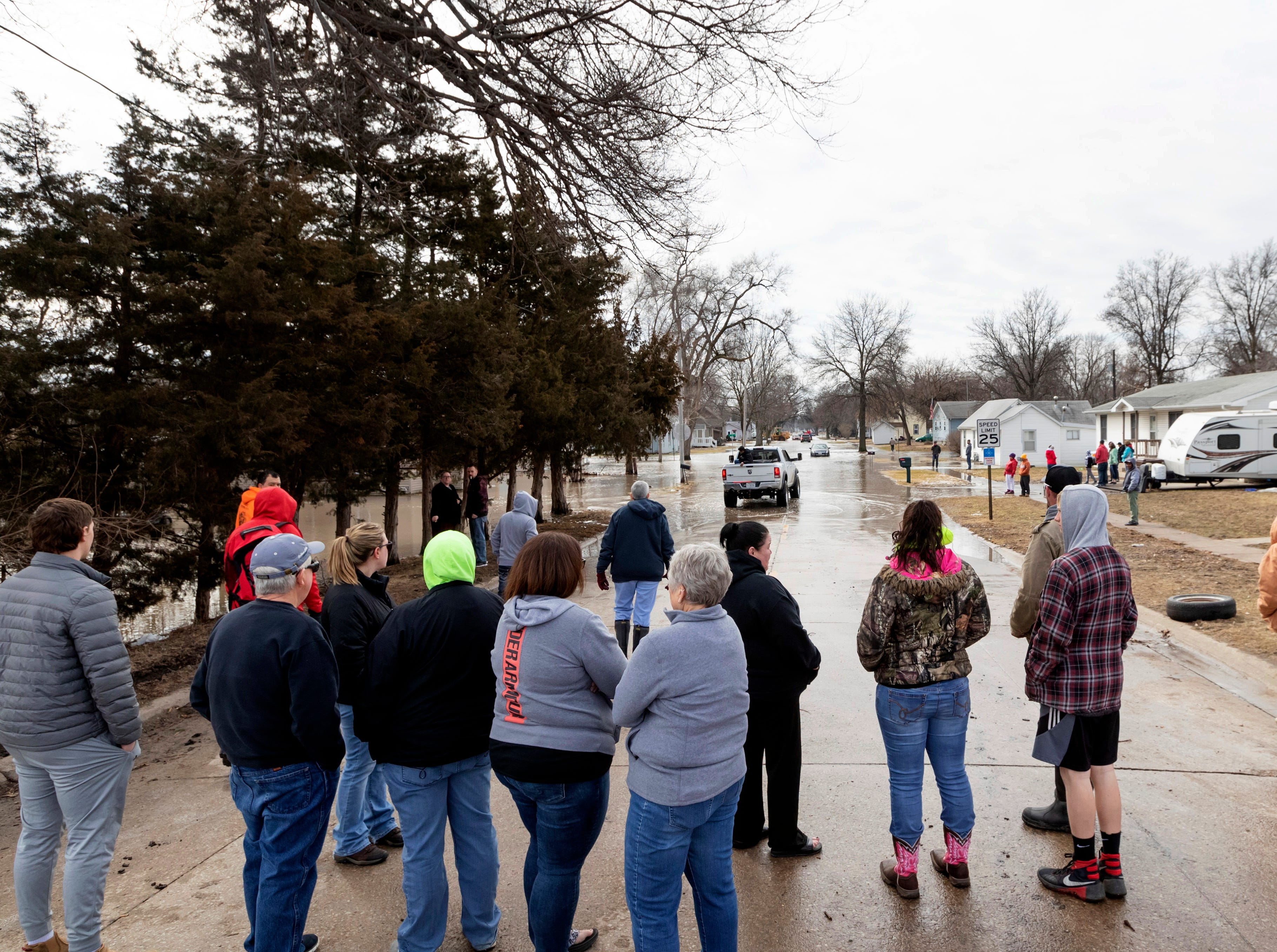 A crowd gathers to watch residents make their way in and out of a flooded neighborhood Sunday, March 17, 2019, in Omaha, Neb. Hundreds of people were evacuated from their homes in Nebraska and Iowa as levees succumbed to the rush of water.
