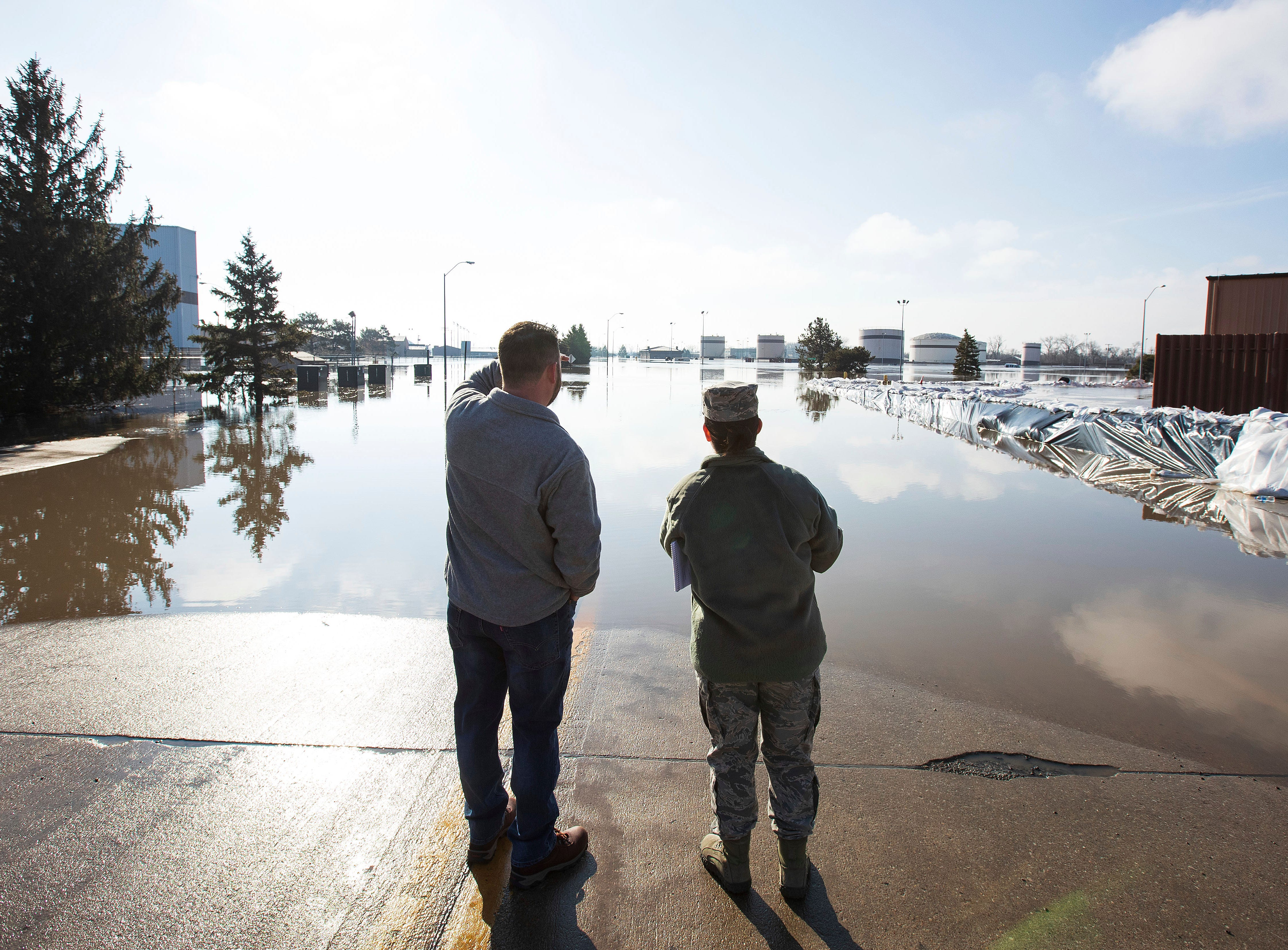 Luke Thomas and Air Force Tech Sgt. Vanessa Vidaurre look at a flooded portion of Offutt Air Force Base Sunday, March 17, 2019, in Bellevue, Neb.