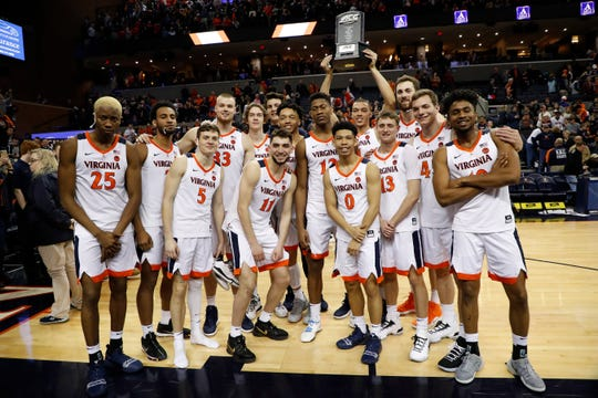 Virginia players celebrate with the ACC regular season championship trophy after their defeat of Louisville on March 9, 2019.