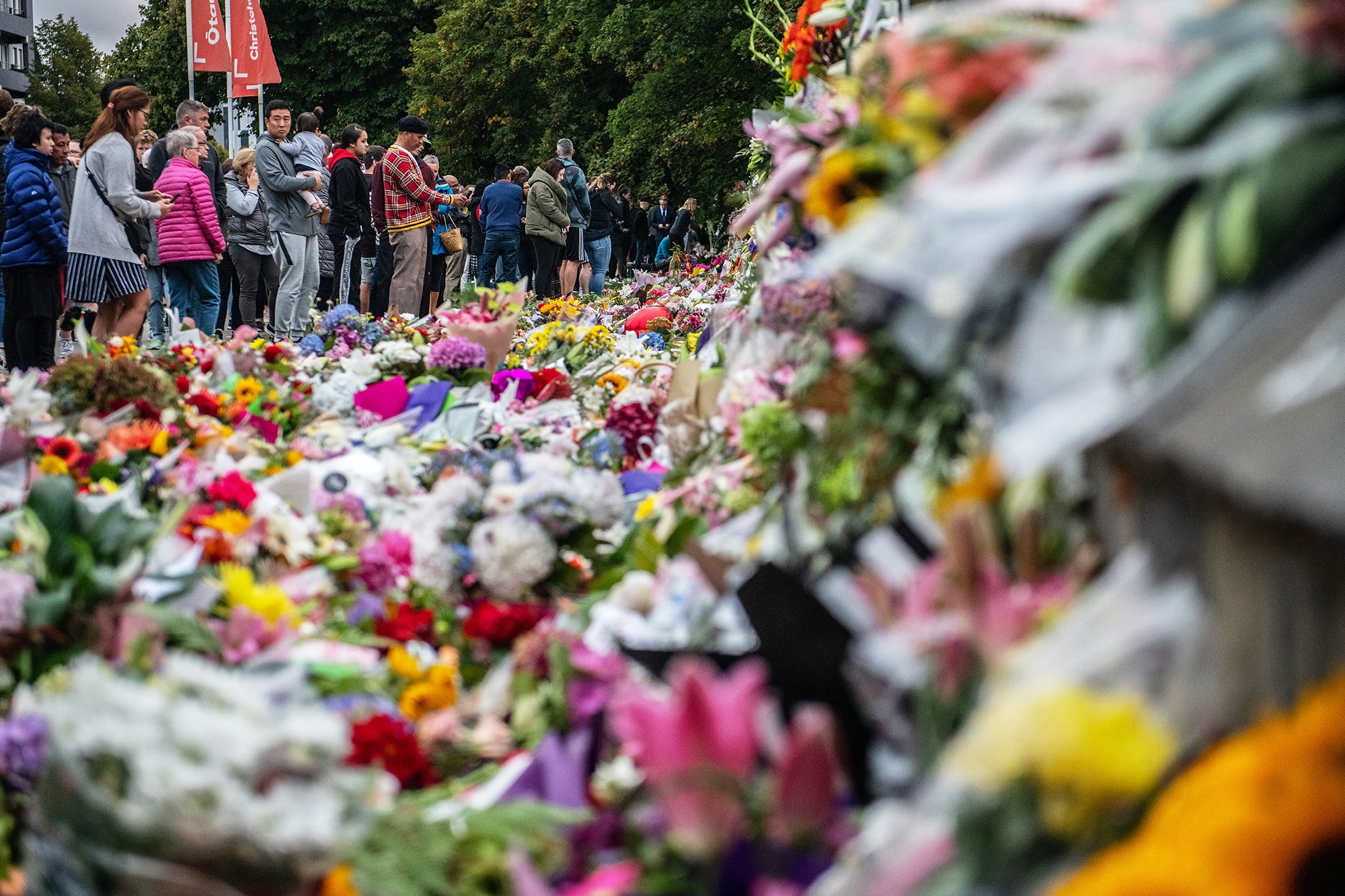 People pause next to flowers and tributes by the wall of the Botanic Gardens on March 17, 2019 in Christchurch, New Zealand.