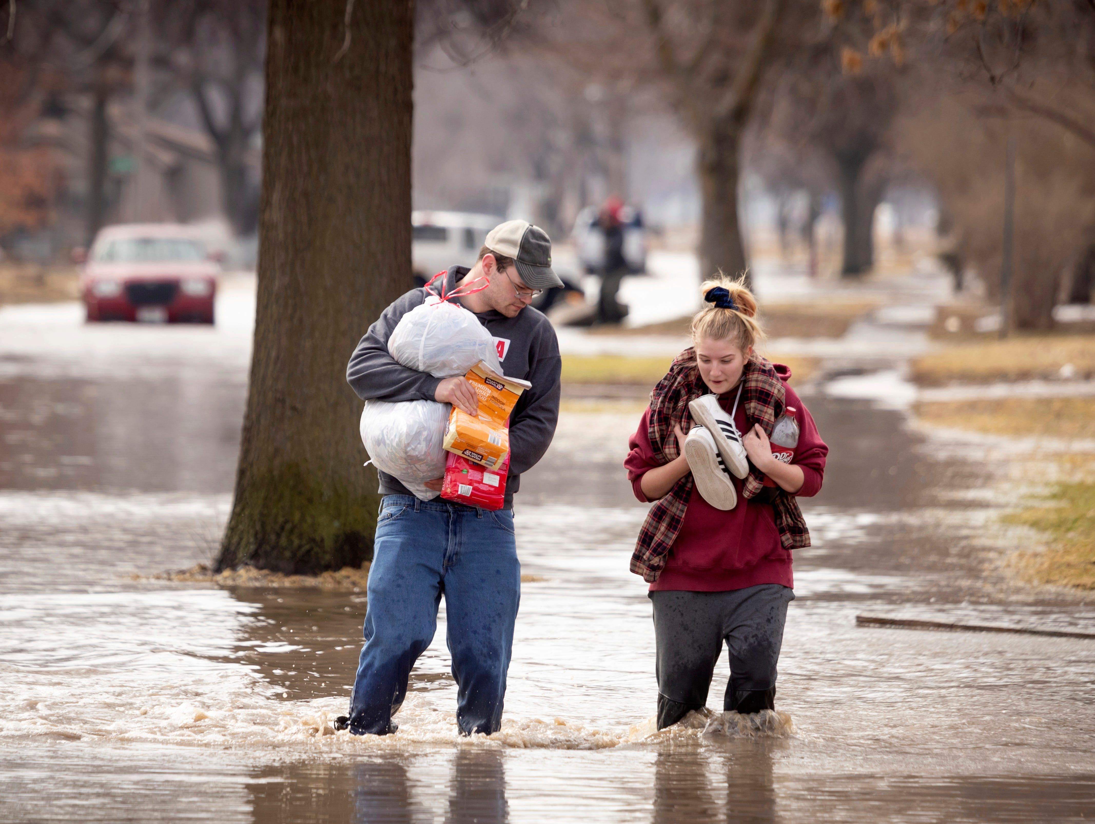 Anthony Thomson, left, and Melody Walton make their way out of a flooded neighborhood Sunday, March 17, 2019, in Fremont, Neb. Hundreds of people were evacuated from their homes in Nebraska and Iowa as levees succumbed to the rush of water.
