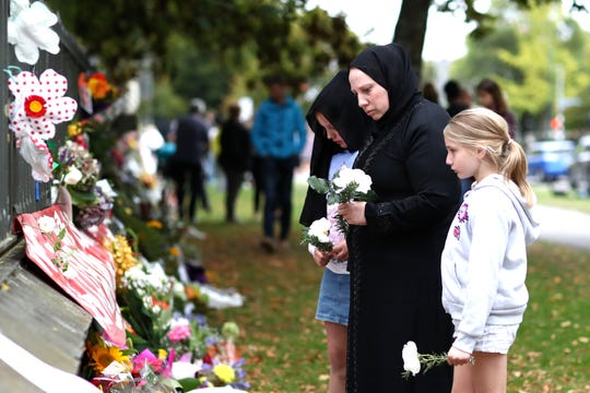 Members of the Muslim community  place flowers at the memorial wall at the Botanic Gardens on March 17, 2019, in Christchurch, New Zealand.