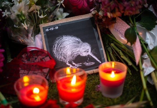 Candles burn next to a picture of a weeping Kiwi that has been laid amongst other tributes by the wall of the Botanic Gardens on March 17, 2019 in Christchurch, New Zealand.