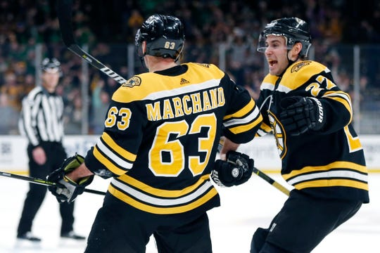 d91ba019a1db0 Boston Bruins  Brad Marchand (63) celebrates with John Moore (27) after