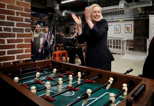 Democratic presidential candidate Sen. Kirsten Gillibrand celebrates her foosball victory at a campaign meet-and-greet on March 15, 2019, at To Share Brewing in Manchester, N.H.
