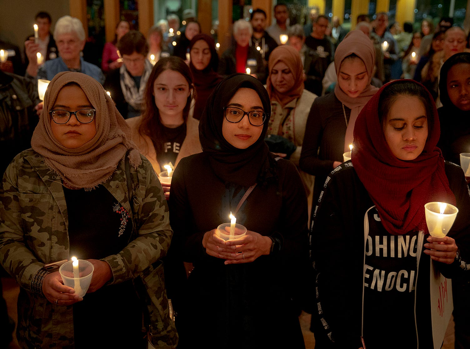 From left, Syeda Sabeera, Sumaiya Syed and Amina Choudhury stand with candles during a prayer service at St. James Episcopal Church on Saturday, March 16, 2019, in Austin, Texas. The service was held in honor of those killed and injured in Friday's mass shooting at two mosques in Christchurch, New Zealand.