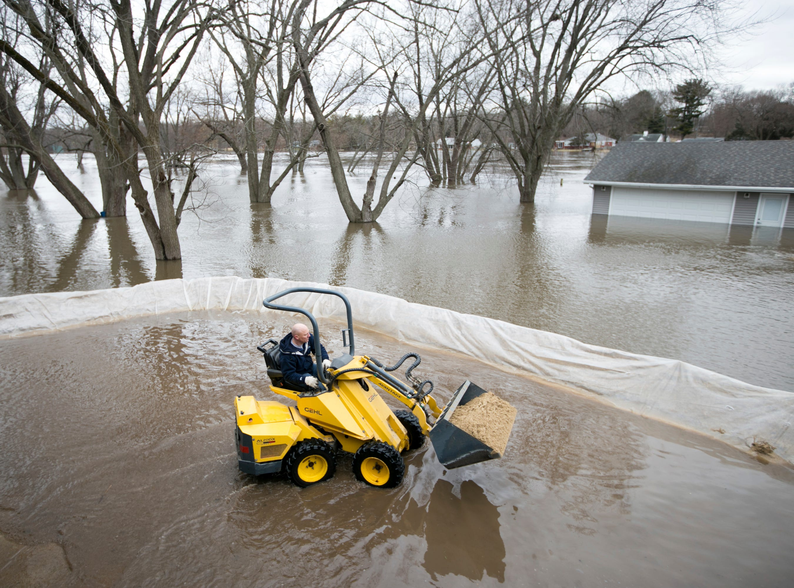 James Snider drives a mini front-end loader to carry sand while building a berm with friends around his Ventura Boulevard home on Friday, March 15, 2019, in Freeport, Ill. Rising waters along the Pecatonica and Rock rivers have flooded homes in northern Illinois.